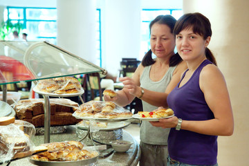 women takes  pastry  in buffet