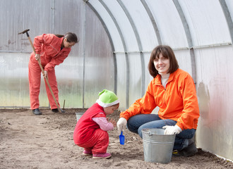 Happy family works in greenhouse