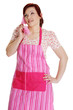 Happy woman in pink kitchen apron talking on the phone.