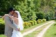 Jeunes mariés s'enlaçant dans un parc - LO
