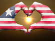 Heart and love gesture by hands colored in liberia flag during b