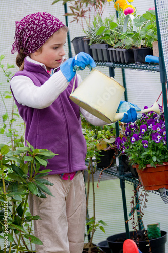 Gardening - lovely girl watering plants in green house