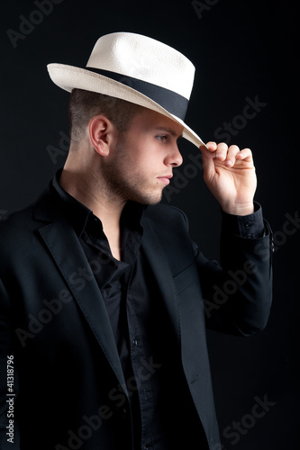 Young man portrait with white hat on black background.