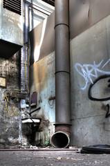 dickes Rohr mit Waschbecken in alter Werkhalle - DDR