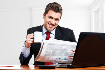 Man reading a newspaper in the office