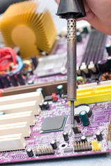Hand with soldering iron over  motherboard