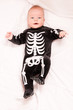 Cute baby portrait in funny skeleton suit isolated on white back