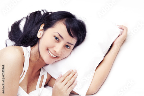 Cute Asian woman smiling on bed