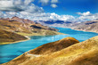 Bright blue lake winds through Himalayas in Tibet on sunny day
