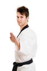 Young man in kimono excercising martial arts, isolated on white