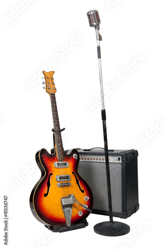 Vintage microphone on stand with guitar and amplifier
