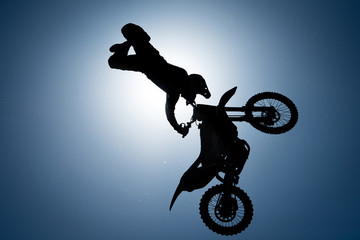 Silhouette of FMX rider against the sun on the sky