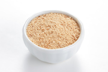 Ground Ginger (Zingiber officinale) in a white bowl on white bac