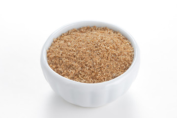 Cumin ground  in a white bowl on white background.