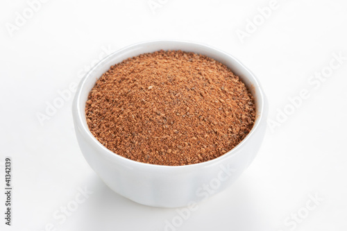 Cinnamon ground in a white bowl on white background.