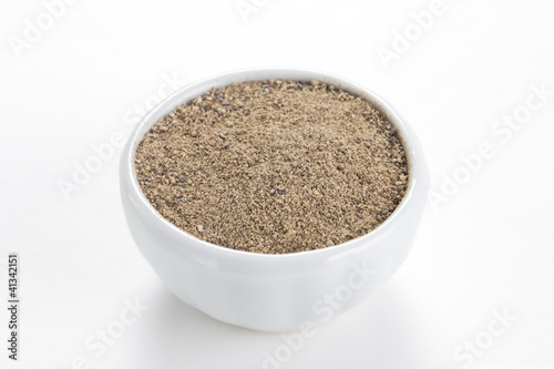 Black pepper ground (Piper nigrum) in a white bowl on white back