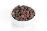 Black pepper (Piper nigrum) in a white bowl on white background.