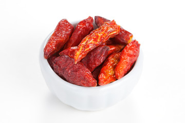 Hot chili peppers in a white bowl on white background