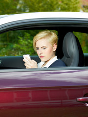 Business woman in her car search online with smartphone