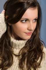 Brunette woman in beige sweater looking aside
