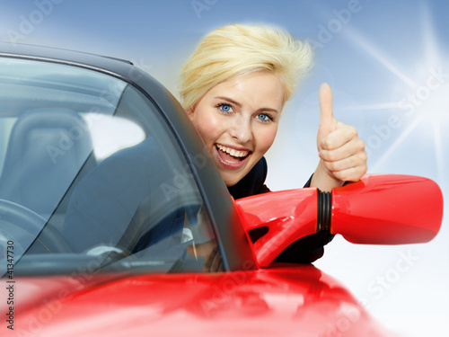 Beautiful 20s driving a red roadster and shows thumb up