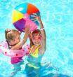 Leinwanddruck Bild - Child playing with ball in swimming pool.