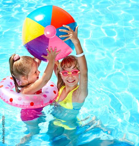 Leinwanddruck Bild Child playing with ball in swimming pool.