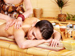 White woman getting massage in bamboo spa.