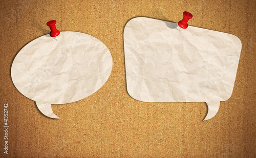 blank speech bubble note paper with push pins on cork board