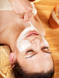 Clay facial mask apply by beautician.