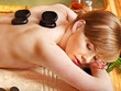 Woman getting stone massage .