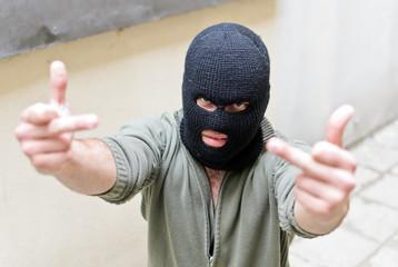 Burglar wearing a mask shows fuck gesture.