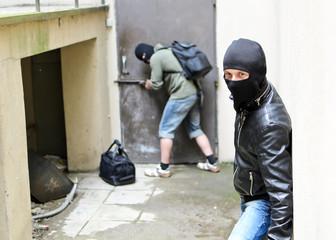 Burglar tries open the door. Second is on the lookout