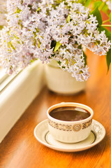 Ceramic cup with coffee and bouquet of lilac