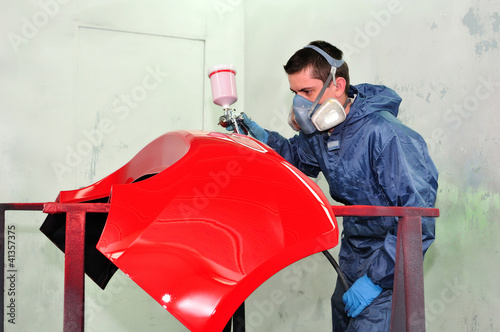 Man painting a red fender.