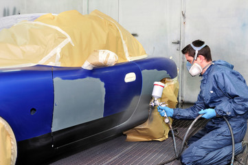 Worker painting a blue car.