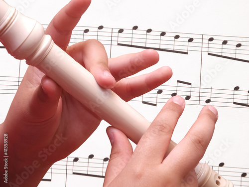 Child playing on white recorder