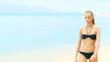 Beautiful woman in bikini walking on the tropical beach