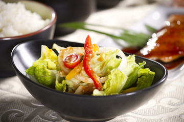 salad, colorful vegetable in black salad bowl with dressing.