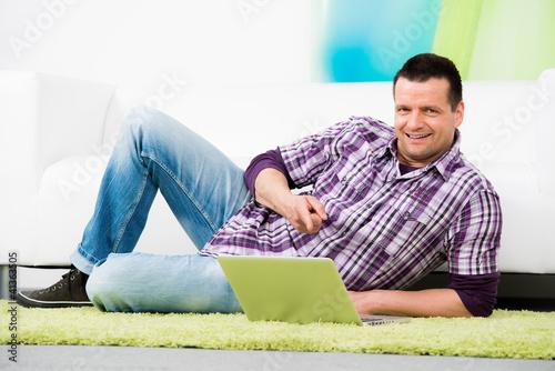 attraktiver mann zeigt auf sein notebook
