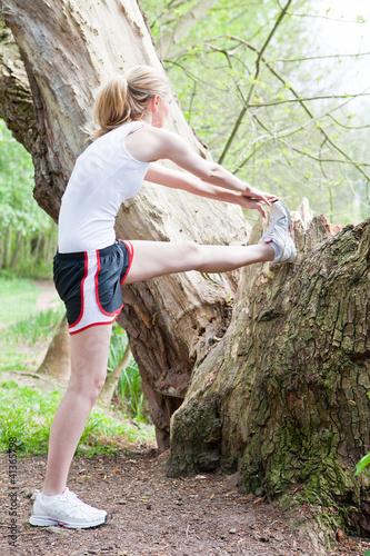 Junge Frau geht auf einem Waldweg joggen