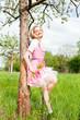 Junge Frau mit einem rosa farbenen Dirndl in einer grünen Wiese
