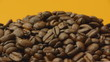 A pile of roasted coffee beans rotating on orange background