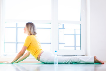 Pretty young woman doing YOGA exercise at home