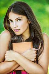 woman with bare shoulders holding brown book
