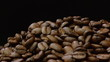 A pile of roasted coffee beans rotating on black background.
