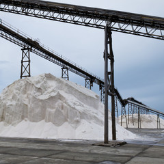 Pile of sea salt under conveyor of saline refinery
