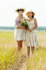 happy women with flowers in summer