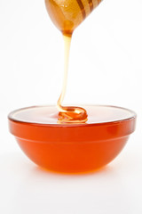 Honey trickle dropping in full honey bowl