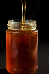 Honey trickle dropping in a honey jar